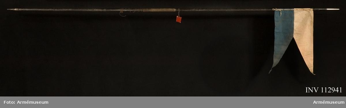 Grupp D I. Spjutbladet har kvadratiskt tvärsnitt. Holken är upptill på en längd av 7,3 cm konisk, men därefter cylindrisk. På spjutbladet är ett krönt W, 90 och en stämpel inslagna. På holken finns bokstäverna M. D. R och K samt en sexuddig stjärna.  Skaftet är av stålrör. Doppskon är av stål och upptill cylindrisk på en sträcka av omkring 1 cm, men i övrigt konisk med tvärt avskuren spets.  Upptill på skaftet finns 6  mässingsöglor, vid vilka flaggan skulle fastgöras. 160 cm  ovanför lansens nedre ände går en mässingsring kring skaftet och nedanför denna ring är skaftet på en sträcka av 28,5 cm lindat med snören. På doppskon finns en stämpel.  Hela lansen, med undantag av spjutbladet är svartmålad.  Mått: Spjutbladets längd 13 cm. Spjutbladets bredd nedtill 1,11 cm. Holkens längd 11 cm. Doppskons längd 9 cm.