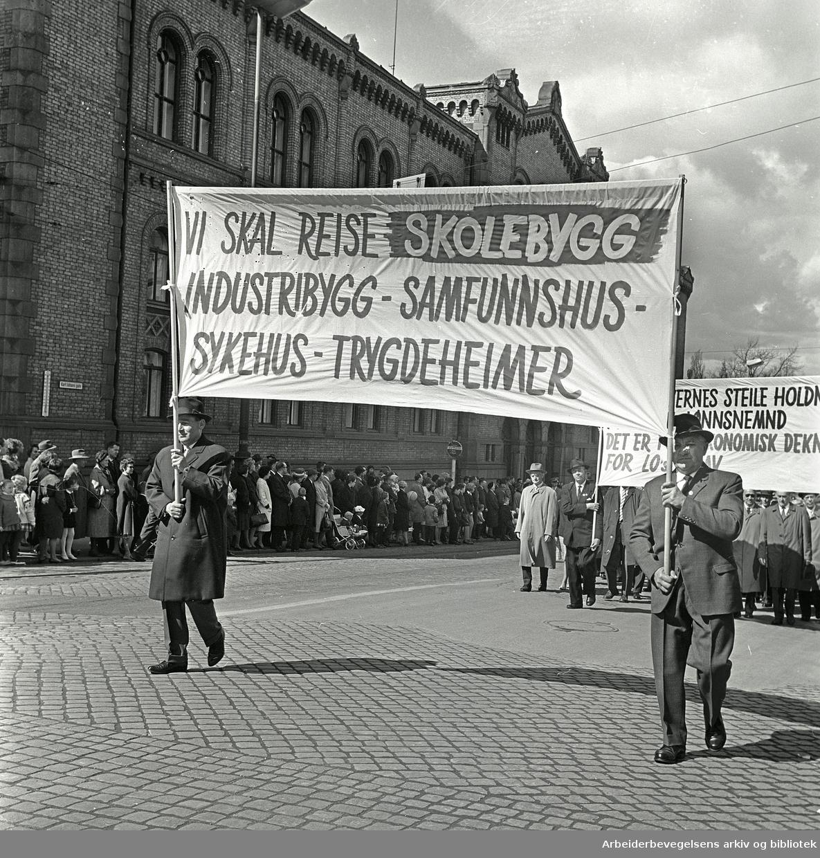 1. mai 1964 i Oslo.Demonstrasjonstoget i Karl Johans gate.Parole: Vi skal reise skolebygg - industribygg - samfunnshus - sykehus - trygdeheimer