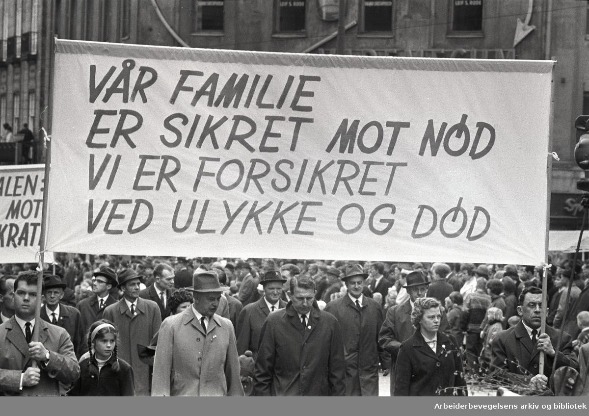 1. mai 1966 i Oslo.Demonstrasjonstoget i Karl Johans gate.Parole: Vår familie er sikret mot nød.Vi er forsikret ved ulykke og død