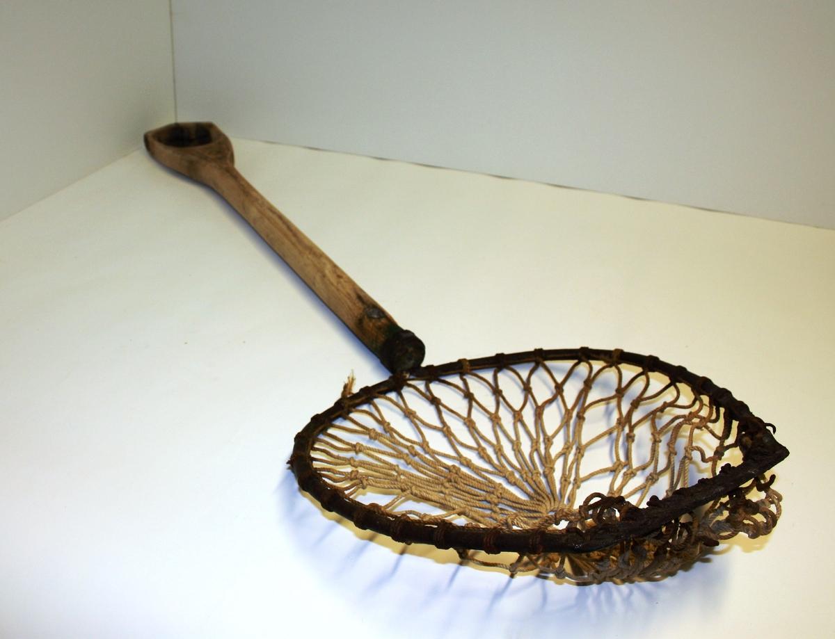 Gjenstanden er en avlang hov med utskore ovalt trehåndtak, oval ramme av jern til å feste nett av grovmønstra tau.