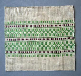 Detta vävprov är vävt i rosengång med en tråd blekt och en tråd oblekt lingarn i solv och rör. Blekt lingarn i tuskaftinslaget och med mönster i grönt och brunt/lila.