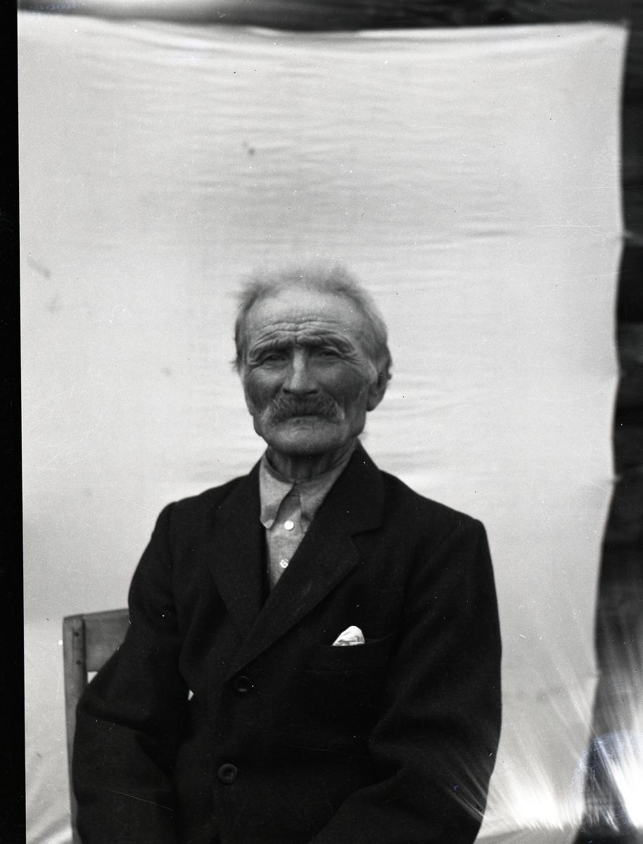 Mann avbildet sittende på en stol foran et oppspent lerret. Han er kledd i mørk dress og skjorte uten slips
