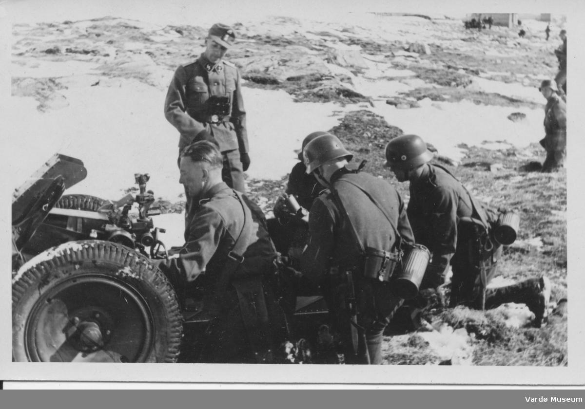 Tyske soldater i Vadsø området 1940-1944. SS-Untersturmführer(fenrik) inspiserer det hele. Soldater som forbereder skyting med kanon