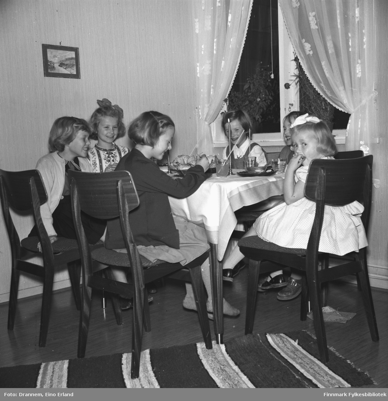 Fem jenter på bursdagsselskap hos Turid Lillian. Jentene sitter ved bordet og drikker saft med sugerør og spiser kaker