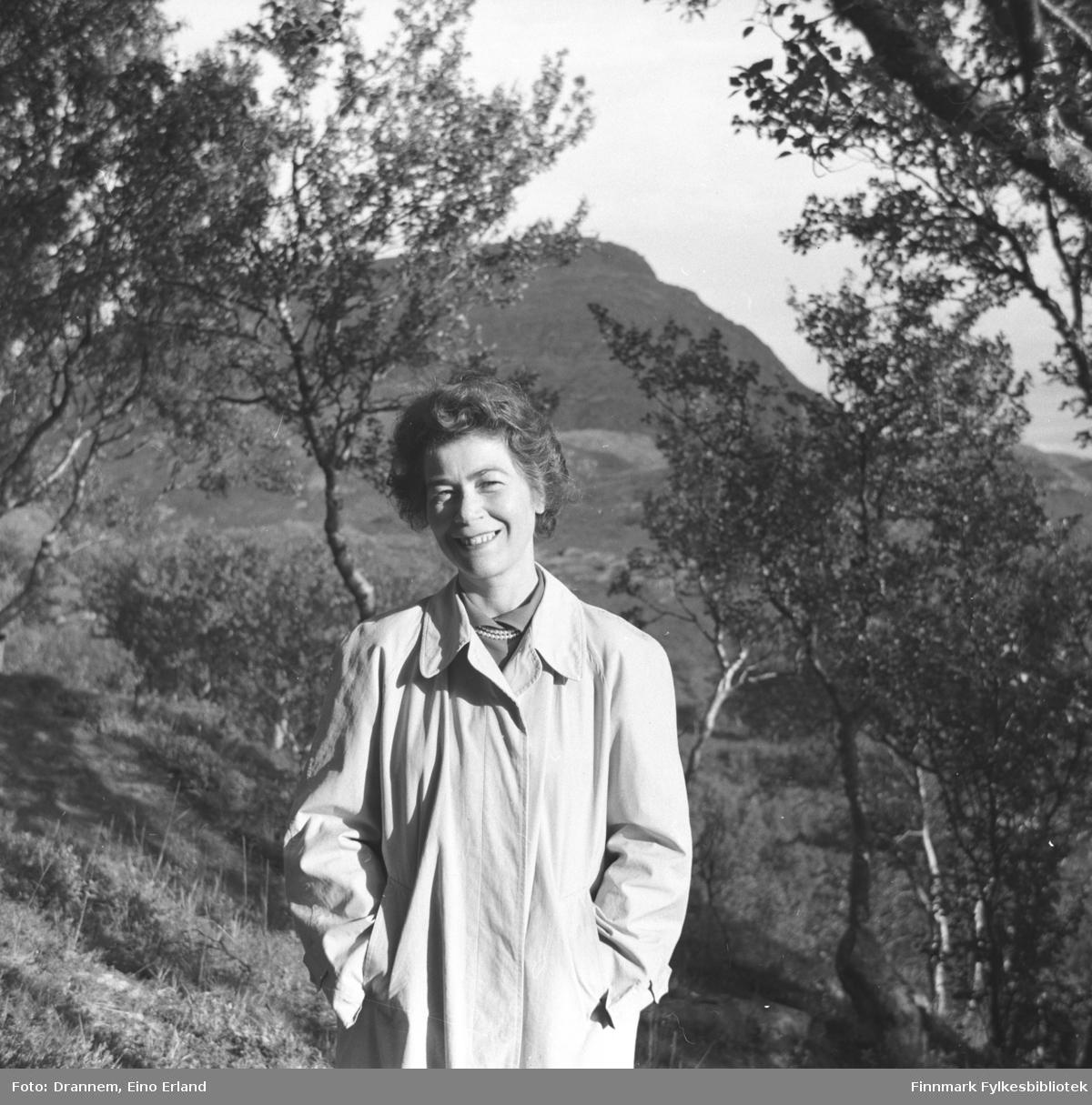 Portrett av Jenny Drannem med trær og fjell i bakgrunn