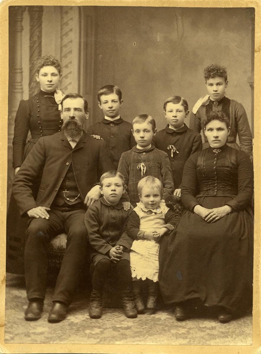 Gruppebilde av en familie med mor og far og syv barn. Alle er iført penklær.