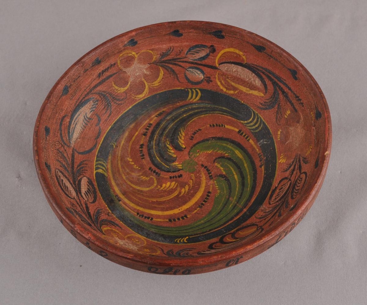 Dreia bolle med raudbrun botnfarge og med fleirfarga rosemåling inni. Påskrift på utsida av øvre del av bollen.