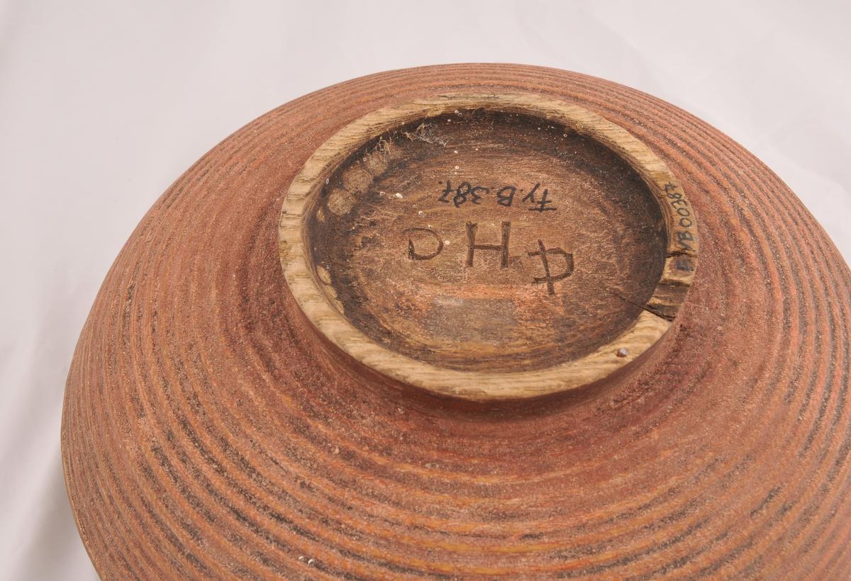 Rund bolle, einsfarga utvendig og rosemåla innvendig. Det er skrift langs øverste kant på både utside og innside.
