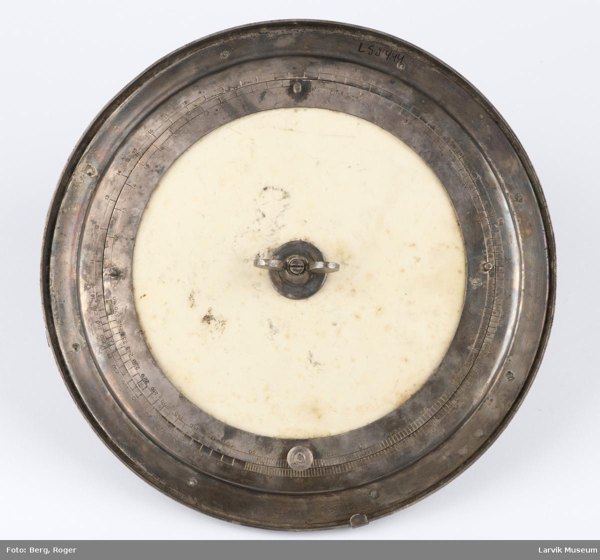Rund metallskive med kompass, midten har opptegnet rutenett med gradstall, 2 visere festet til midten med en vingeskrue