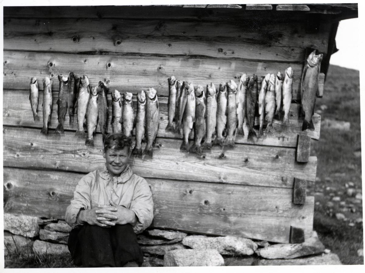 Portrett av en ung mann sittende foran en husvegg. Bak seg henger det en lang rekke med fisk.