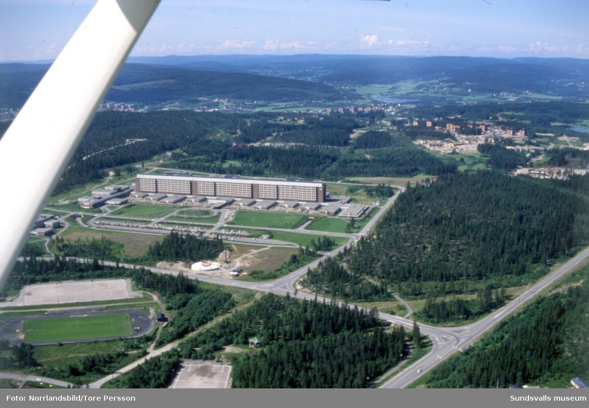 Flygfoto över Sundsvalls sjukhus taget västerut med Baldershovs idrottsplats i nederkant och det pågående bygget av bostadsområdet i Granloholm till höger.