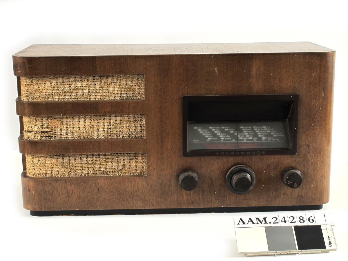 "Radio , Telefunken , ""folkemottaker"".  Kasse bøk , innmat med 2 pærer. Rektangulær kasse med avrundede hjørner og 3 åpne spalter i hjørnet tv. med lyst stoff bak , spaltene går over hjørnet som et ""funkis"" vindu. 3 knotter."