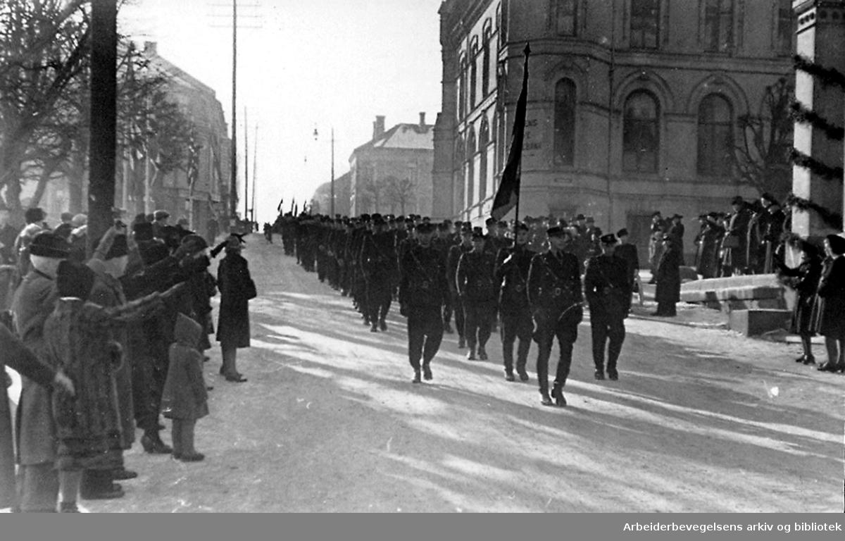 Rikshird marsjerer mens folk langs gaten gjør nazihilsen, Hesselbergs gate i Skien,.1940-45