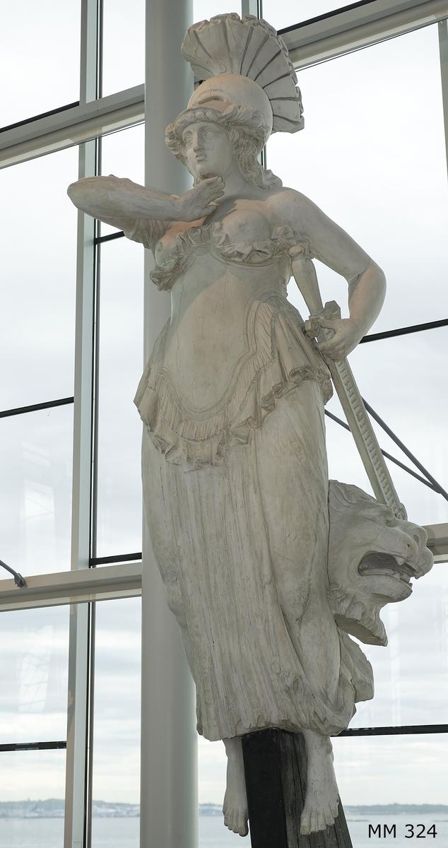 Galjonsbild tillhörande linjeskeppet Fäderneslandet. Hjälmprydd kvinnofigur med kyrass som börjar under brösten. Högra armbågen hålls upp i axelhöjd med handen pekande mot halsgropen. Vänster arm på väg att fatta svärdet. Lejonhuvud bakom vänster lår. Svärd hängande vid vänster sida. Färg: Vit (har alltid varit vit)