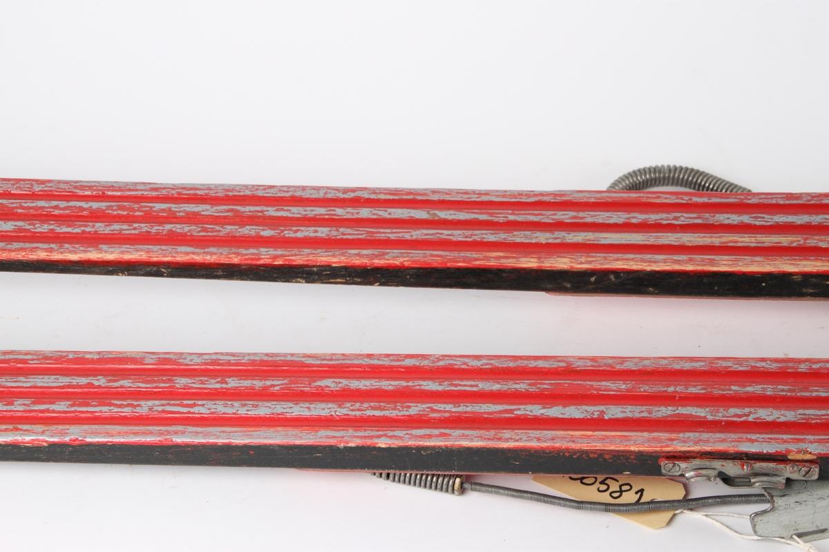 Hoppski i tre fra Hovde Skifabrikk med Kandahar-bindinger, og tre render under.
