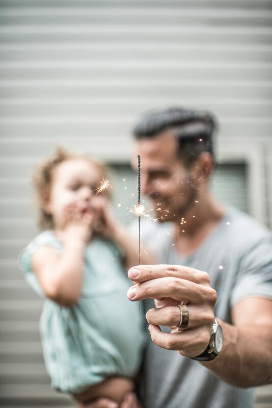 Bildet viser en mann holder et barn og har et stjerneskudd i hånden (Foto/Photo)