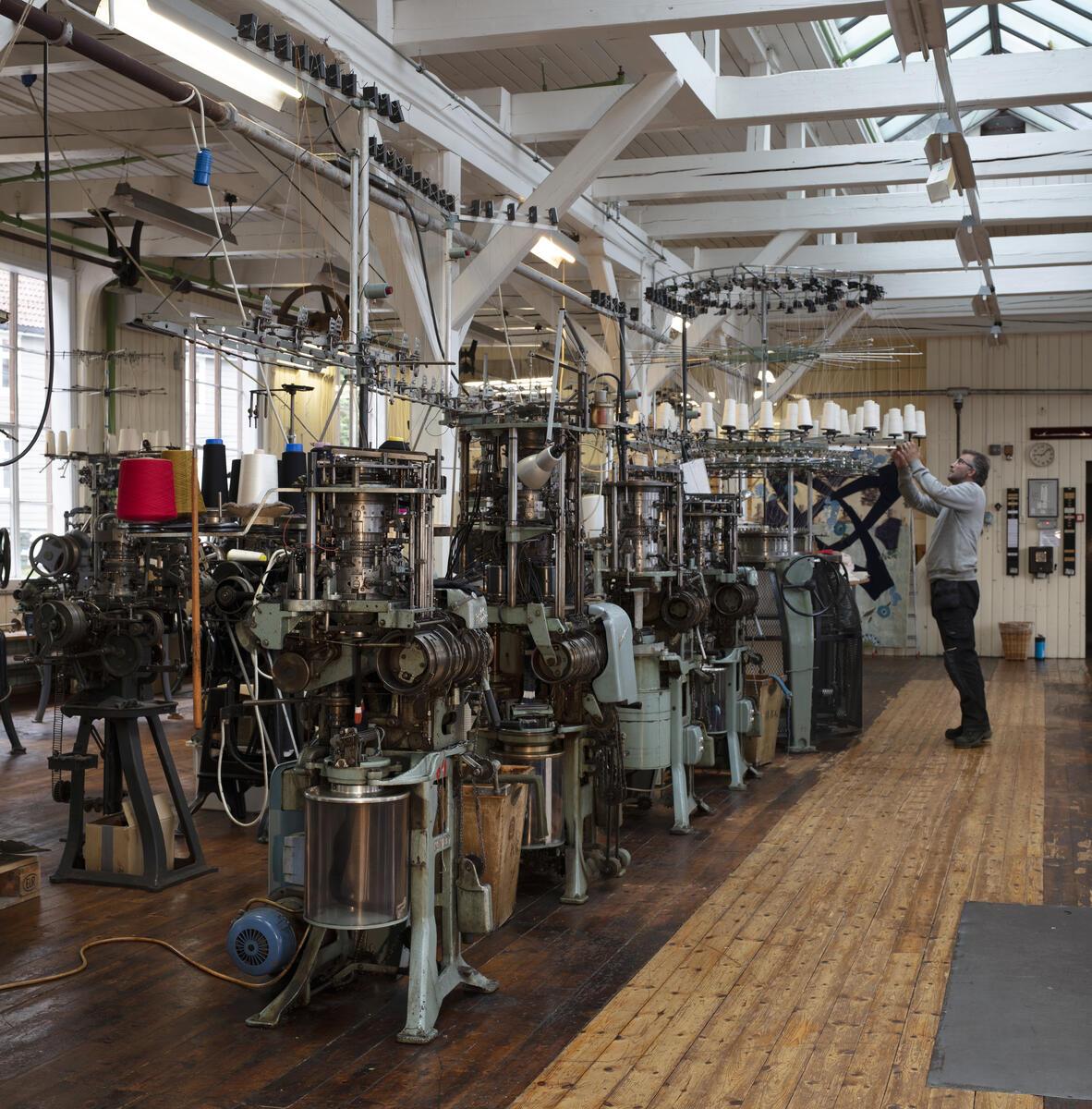 strikkemaskiner i fabrikklokale, mann arbeider med maskin (Foto/Photo)