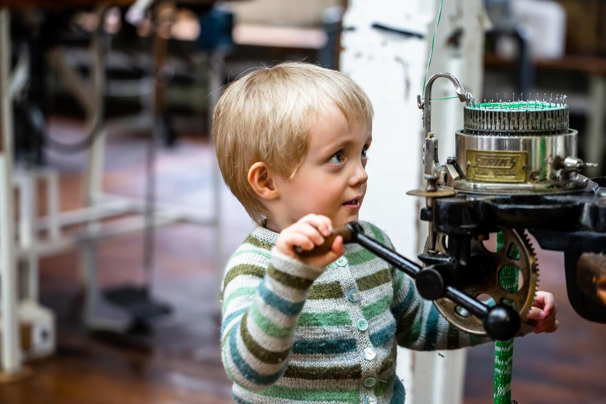 blond gut med stripete strikkegenser sveivar på maskin (Foto/Photo)