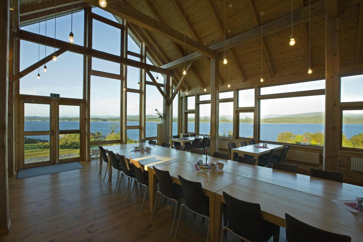 Interiør med langbord, vindauge med utsikt over kystlandskap. Foto (Foto/Photo)