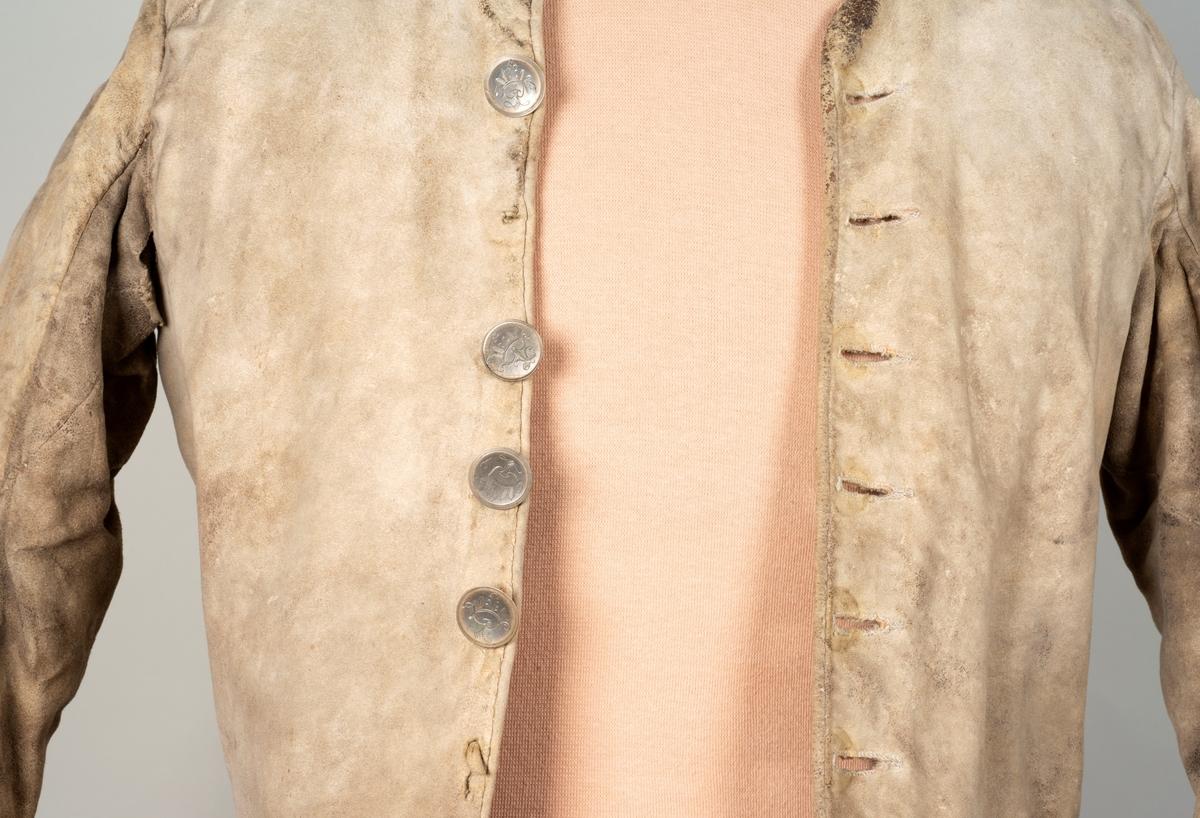 Sid mannstrøye med magebelte. Tynt, oljegarvet skinn foret med ull. Er vannskadet med revner og slitasje på lommer.