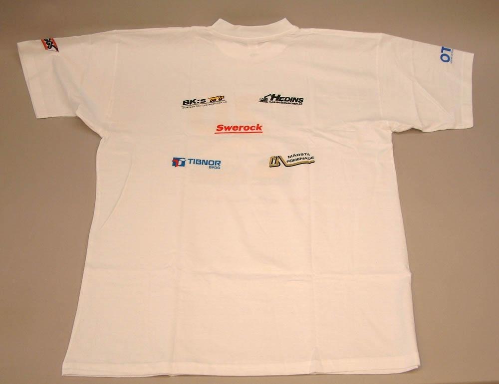 """Vit T-shirt med tryck i olika färger. Text: """"20 minuter Arlanda Express"""", samt en illustration av ett gult Arlanda-expresståg Storlek XXL. Reklam för Arlanda Express på framsidan och sedan olika sponsorers logotyper både på ryggen och på ärmarna."""