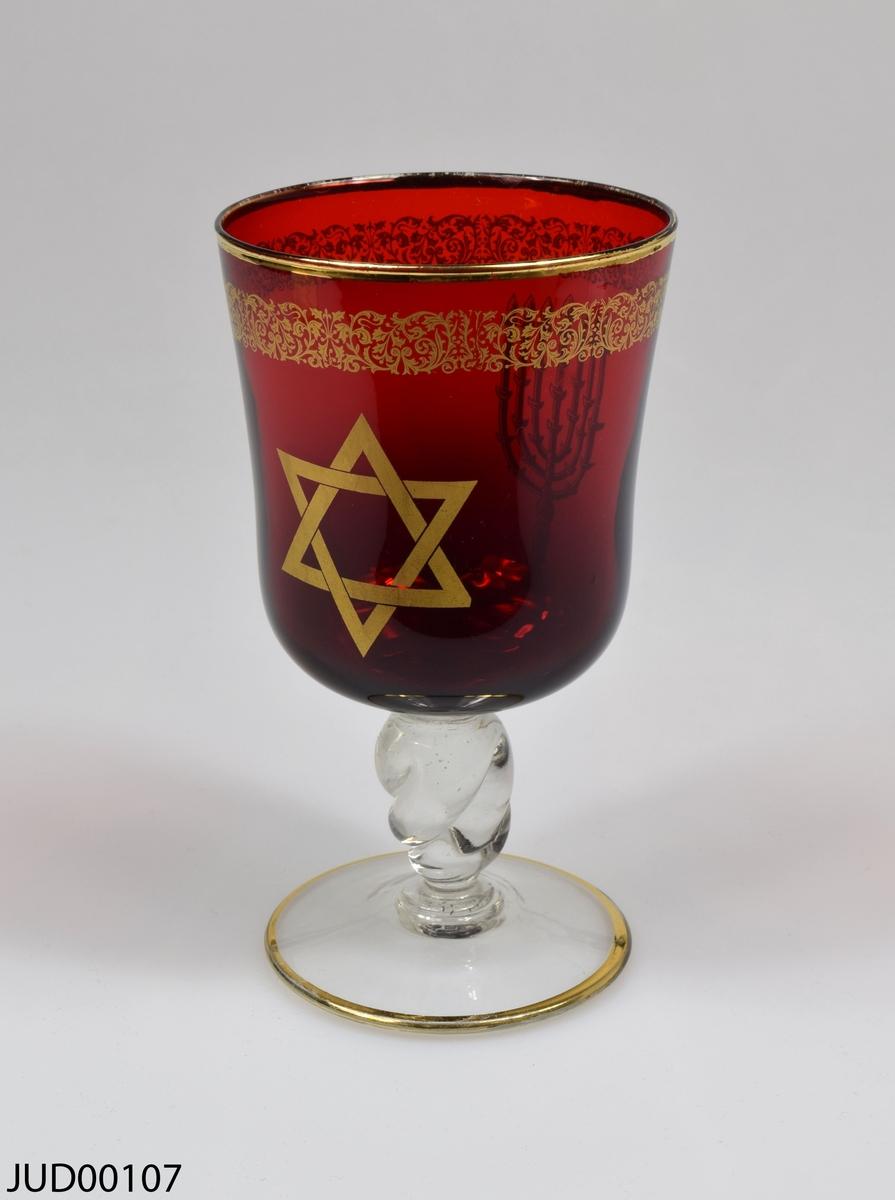 Glasbägare med röd cupa och en transparent, vriden fot. Bägaren är dekorerad med guldfärgad dekor, i form av en davidsstjärna, en menora samt en blomsterbård.