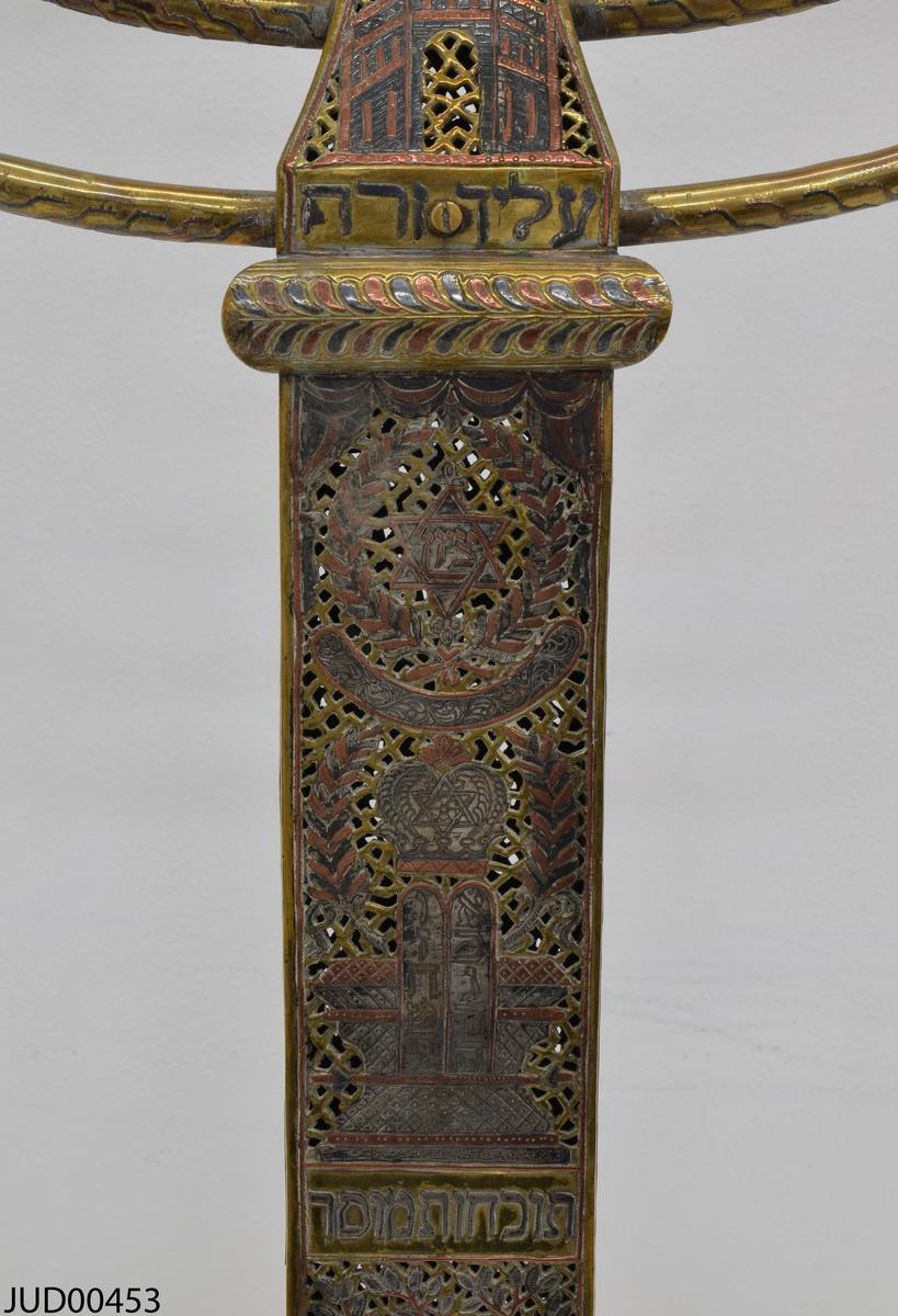 Stor chanukkaljusstake tillverkad av mässing, i form av en obelisk dekorerad genombruten dekor i rött och svart. Davidsstjärna på toppen mellan ljushållarna.