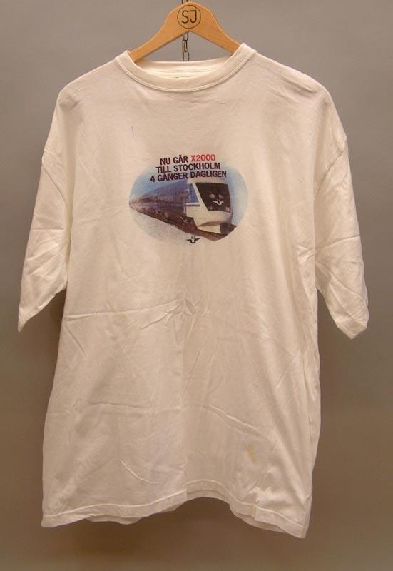 """Vit t-shirt med text """"Nu går X2000 till Stockholm 4 gånger dagligen."""" Bild under av X2000 med en liten svart SJ-logga. På baksidan en räls med texten Ostkustbanan, Härnösand, Sundsvall, Hudiksvall, Söderhamn, Gävle, Uppsala och Stockholm. Storlek XL."""