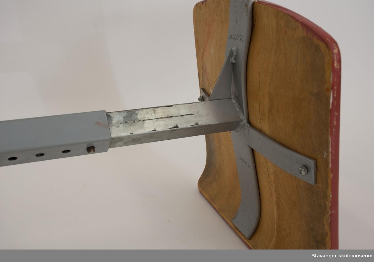 Elevstol av jern og bøyd kryssfiner. Gråmalt st]l og rødmalt kryssfiner i sete og rygg. Er justerbar i høyde.