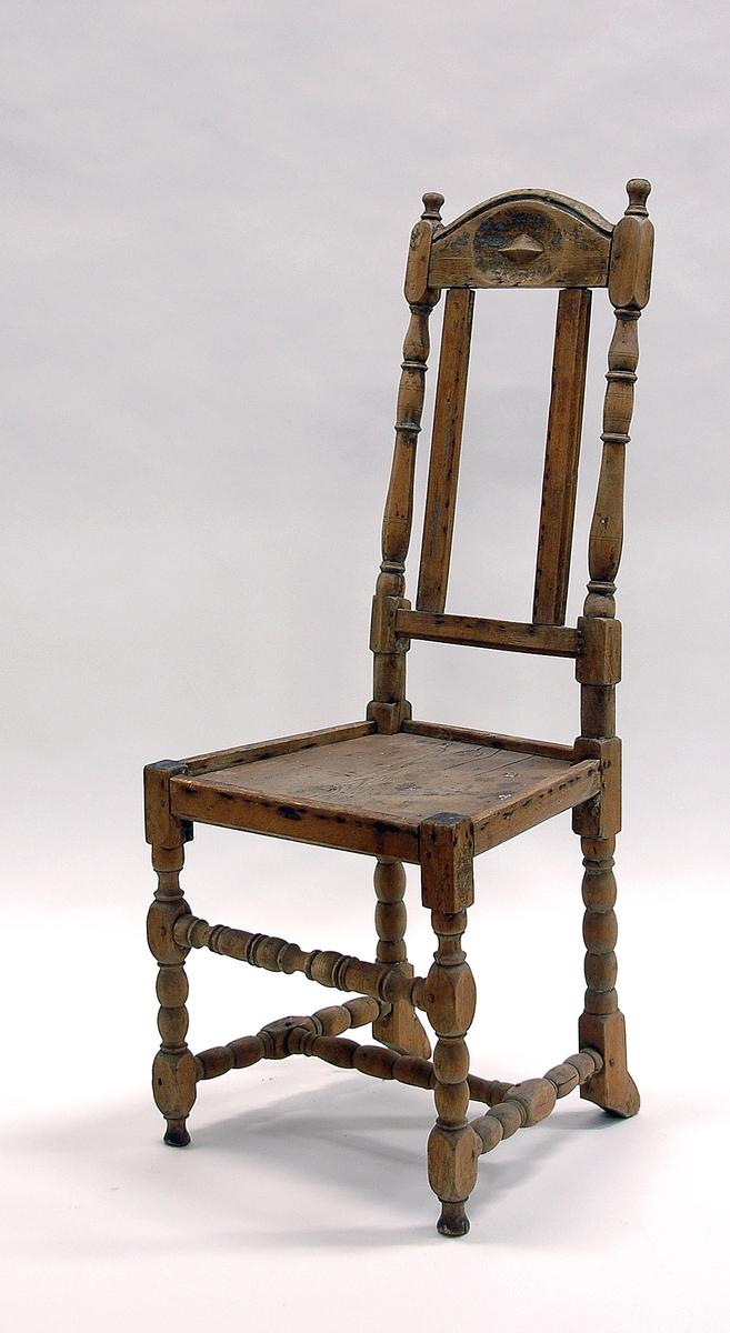 Katalogkort: Stol, s.k. bergsmansstol, hög karolinsk typ, med raka svarvade ben, de bakre något förtjockade och bakåtböjda nertill. Klädsel på rygg och sits saknas. Smal, rak sarg. Upptill på ryggstödet en rektangulär bräda med svängd överkant och med en stjärnliknande utskärning /relief/ i mitten av en oval sänka.   Har varit utst. på museet, rum 13