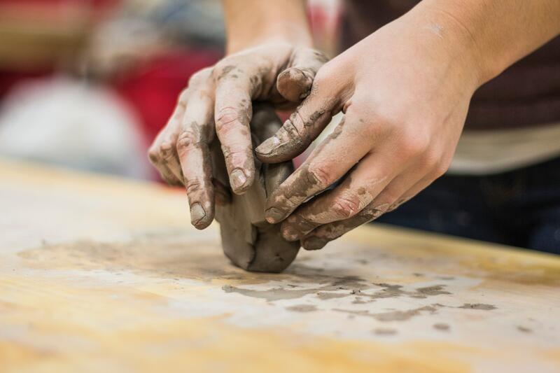 Bildet viser hender som knar leire inne på en benk (Foto/Photo)