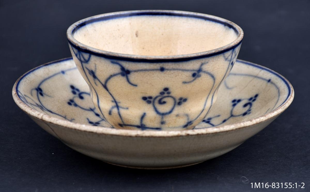 Kaffekopp med fat, koppen utan öra, fajans, vit med blå handmålad dekor.