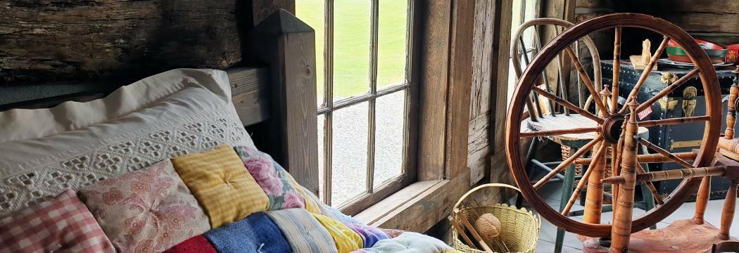 Interiør med rokk og seng med lappeteppe (Foto/Photo)
