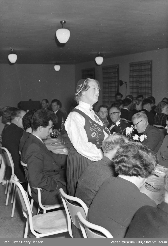 Kvinne, ukjent, holder tale på festmiddag. Bildet er trolig tatt ved innvielsesfesten for Vadsø folke- og framhaldsskole 28.10.1956. Kilde: Melding om Vadsø folke- og framhaldsskole for skoleårene 1951/52-1959/1960. Vadsø 1962.