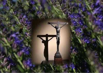 Statue av korsfestet Jesus på en bakgrunn av blå isop.. Foto/Photo