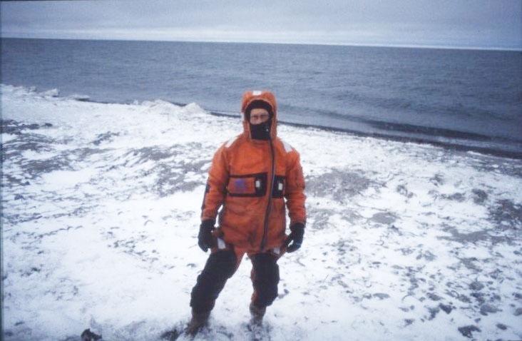 Porträtt av en man i överlevnadsdräkt på Vitöns snötäckta strand.
