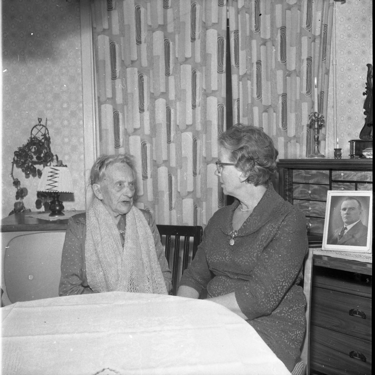 En äldre dam sitter i en hemmiljö och pratar med en något yngre dam. Ett porträtt av en man står på chiffonjen bredvid dem.