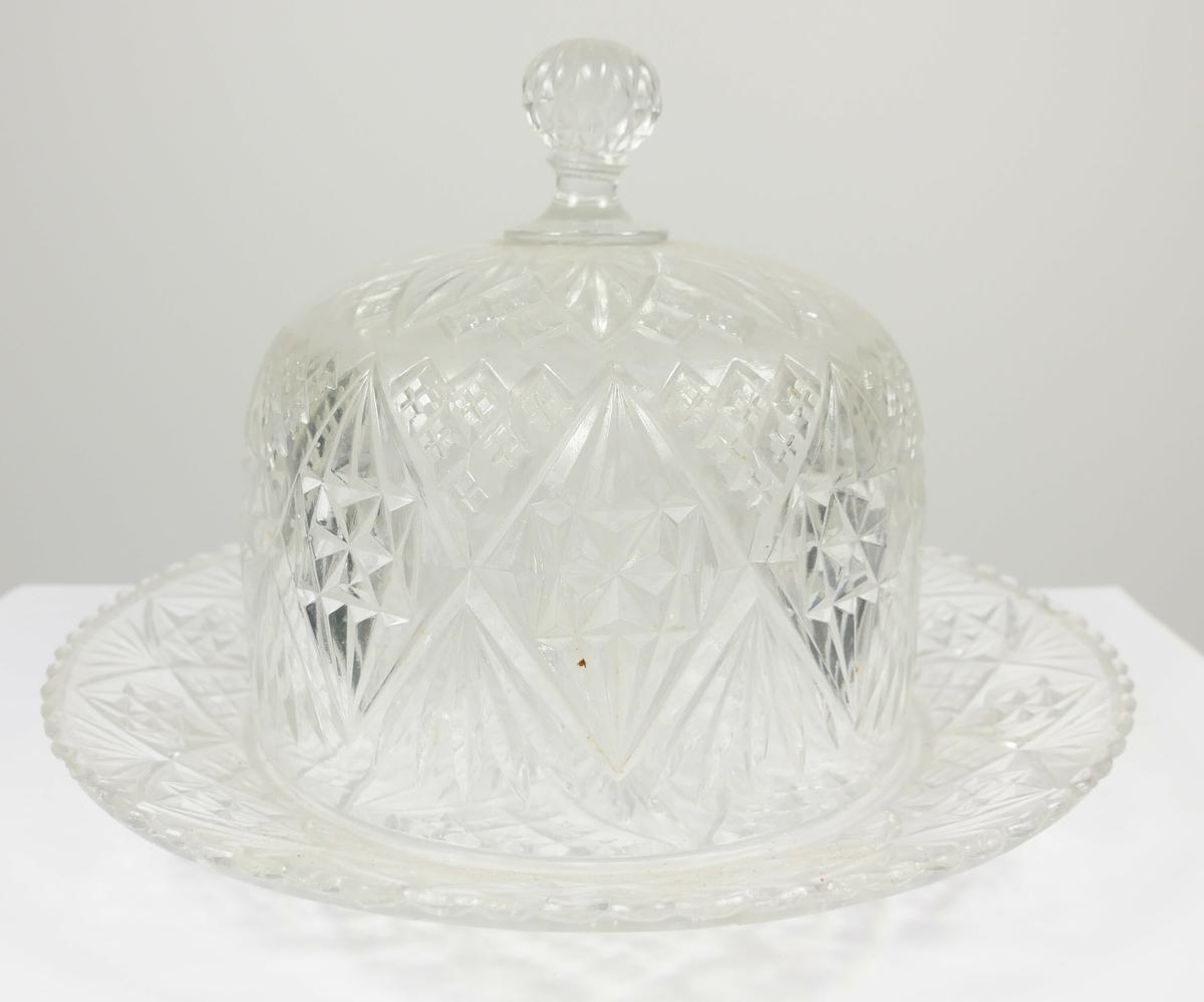 Rund glassklokke av glass med håndtak midt på øverst, klokken står på en rund skål av samme materiale og med samme dekor.