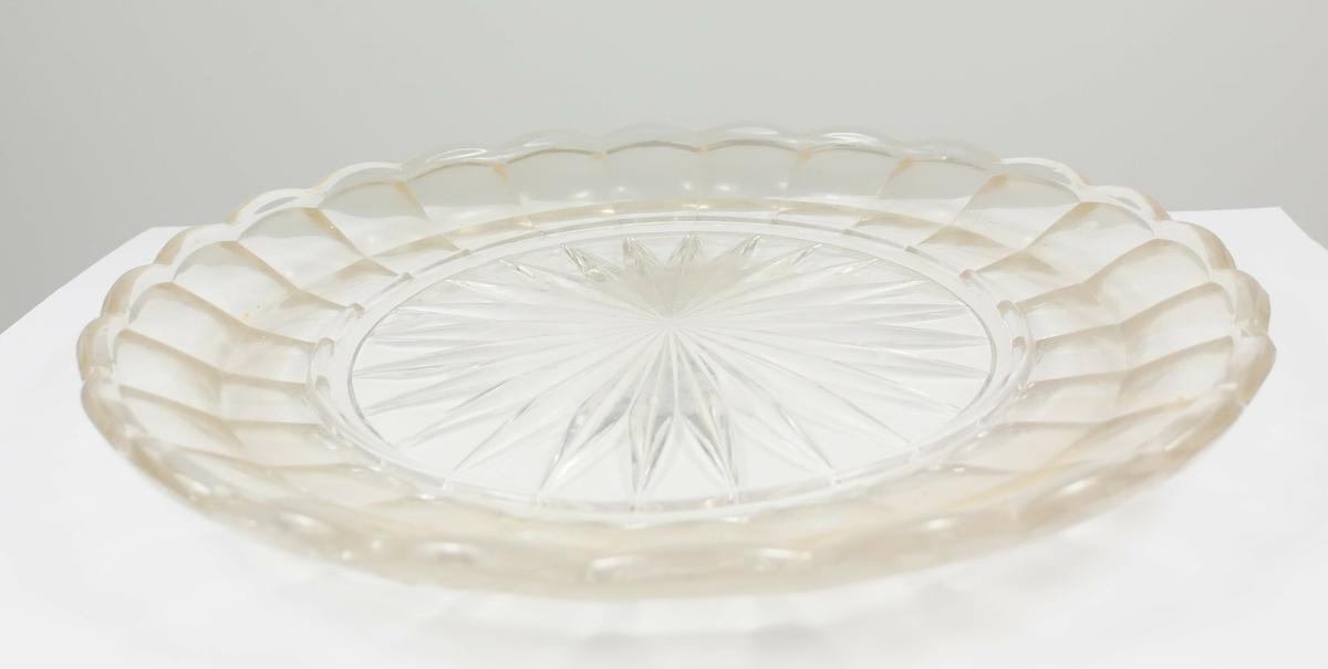 Rund klokke av glass med håndtak øverst. Rundt fat av glass med stjerneformet mønster midten.