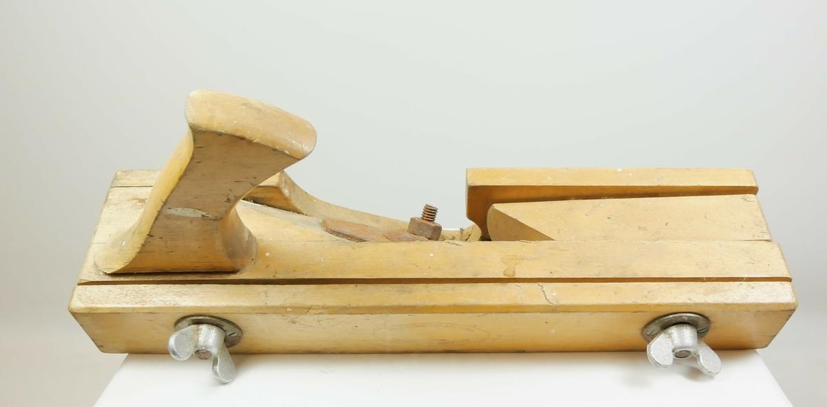 Høvel i tre med håndtak. En større trelengde i midten med en høveltann i metall med en bolt. På hver side er det mindre trelengder. Den ene har to skruer som kan reguleres.