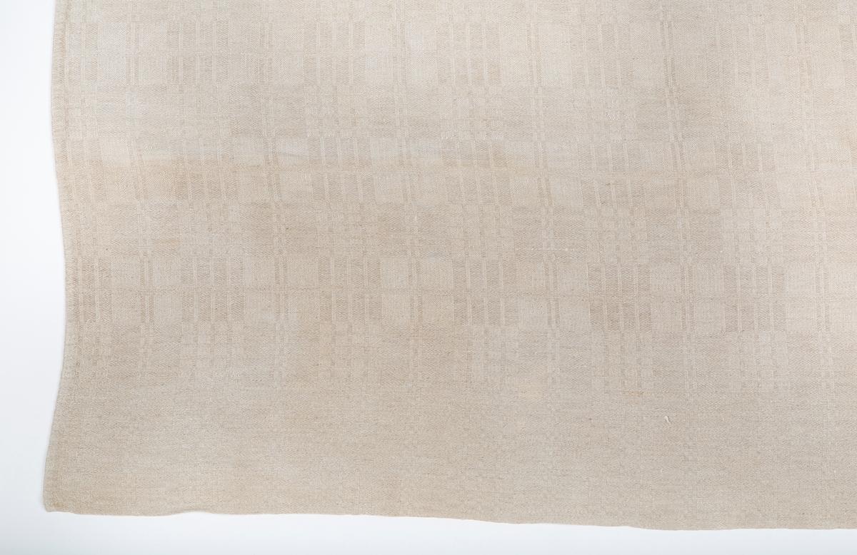 Duk. Linduk. Kvadratisk, Sydd sammen av 2 vevlengder. Rutemønster, damaskveving.   Giver Fanny Aschim har opplyst at duken er laget av lin dyrket på Gaavim, håndvevet av Anne Helene, Anette eller Amalie Gaavim. Duken var også med på Akershus Bondekvinnelags tekstilutstilling på Norsk Folkemuseum 1953/54, merkelapp fra utstillingen mangler.