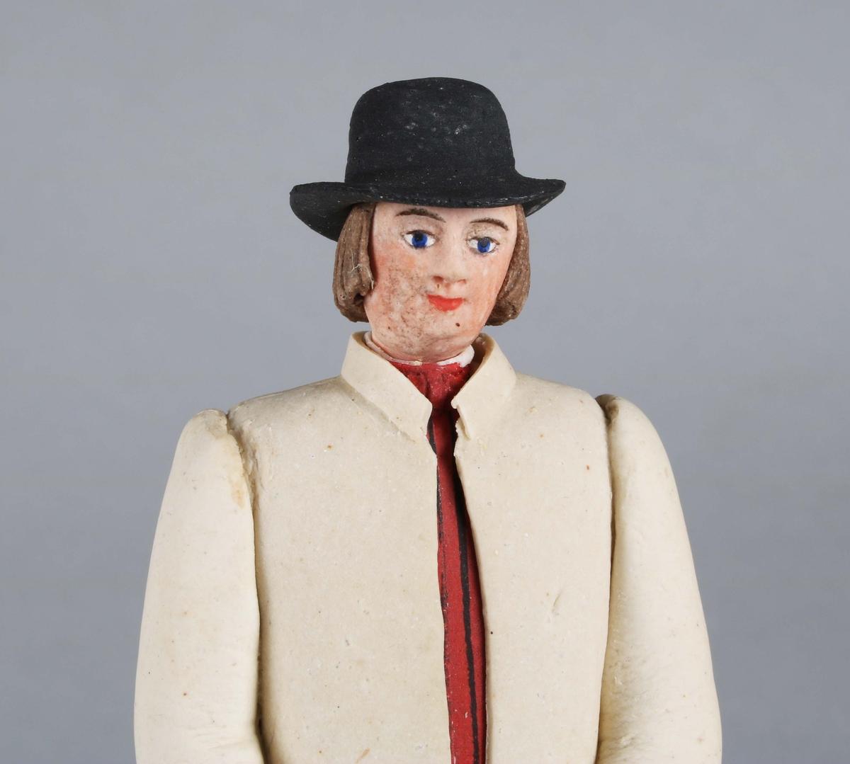 Dragantarbete. Mansfigur. Allmogedräkt. Stående mansfigur iförd svart hatt med platt kulle och rakt brätte, ej så brett. Rakt kortklippt hår. Halsduk i halsen. Ljus  ytterrock med långa ärmar, i vars mittparti synes randig väst, röd och svart. Knäkort, ljus, aprikosfärgad byxa, med vita tofsbollar vid knäet. Vita strumpor. Svarta skor. Brun promenadkäpp. Står på grått underlag bestående av åttkantig platta.  Tillverkad av Hilda Boström (1822-1903), sockerbagare, Borås.  Litt: Se Årsbok 1963, sidan 44.  Funktion: Prydnadsfigur