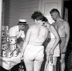 Personer vid en konsumbutik, under sommartid.