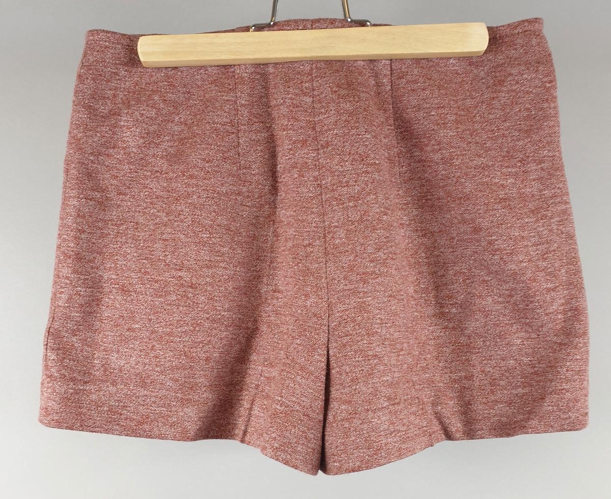 Kort jakke med shorts av akryll. Jakka har lange ermer, skjortekrage og lukkes med fire metallknapper i front.  Brystlomme med klaff på hvert forstykke. Kortbukse med elastikk i livet.