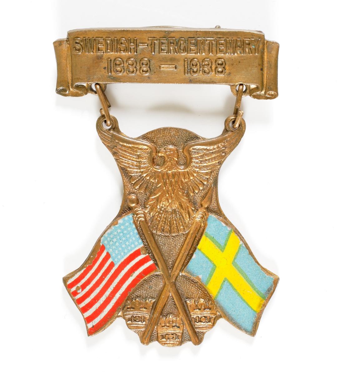 """Nålmärke bestående av en överdel försedd med texten """"SWEDISH-TERCENTENARY 1638-1938"""", samt en underdel som är sammanlänkad med två öglor. Den undre delen består av två korslagda fanor, den amerikanska och den svenska, samt upptill den amerikanska nationalörnen och nedtill de tre svenska kronorna."""