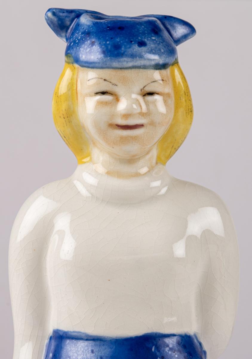 Figur av flicka med namnet Gretchen, blont hår, blå långbyxor, vit tröja och blå hatt, med ena handen på ryggen och den högra längs sidan. Handmålad. Stämpeltryck på undersidan med Gefles loga med tre rundugnar samt namnet GRETCHEN.