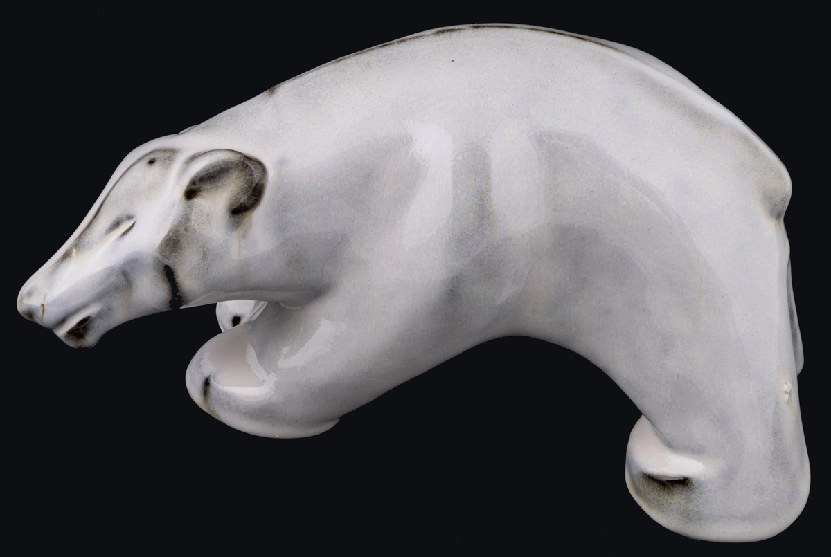 Figurin föreställande stående isbjörn, röd stengodslera, vit fajansglasyr. Formgiven av Maggie Wibom för Gefle 1933-34, signerad med initialer på höger bakben. Inga fabriksstämplar.