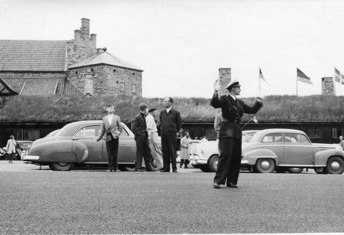 En polis står mitt i vägen och dirigerar trafiken vid Gyllene Utterna. Bakom honom parkerade bilar, några män och ungdomar. Pojken till vänster blåser möjligen såpbubblor. Det är folksamling i samband med en solförmörkelse.