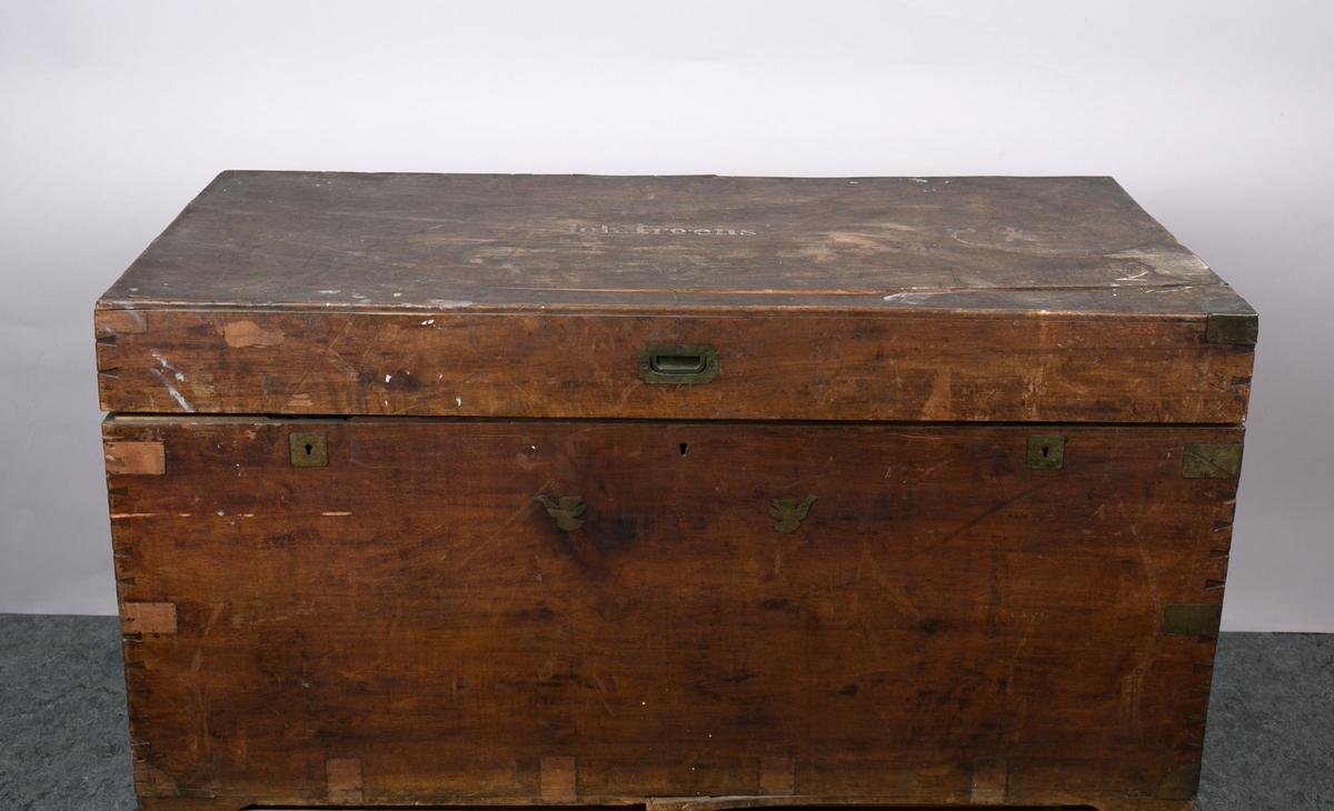 Reisekiste med flatt lokk, to låser og metallbeslag på sidene. Dekorert med to fugler i metall på forsiden. Innsats i tre som kan løftes ut.