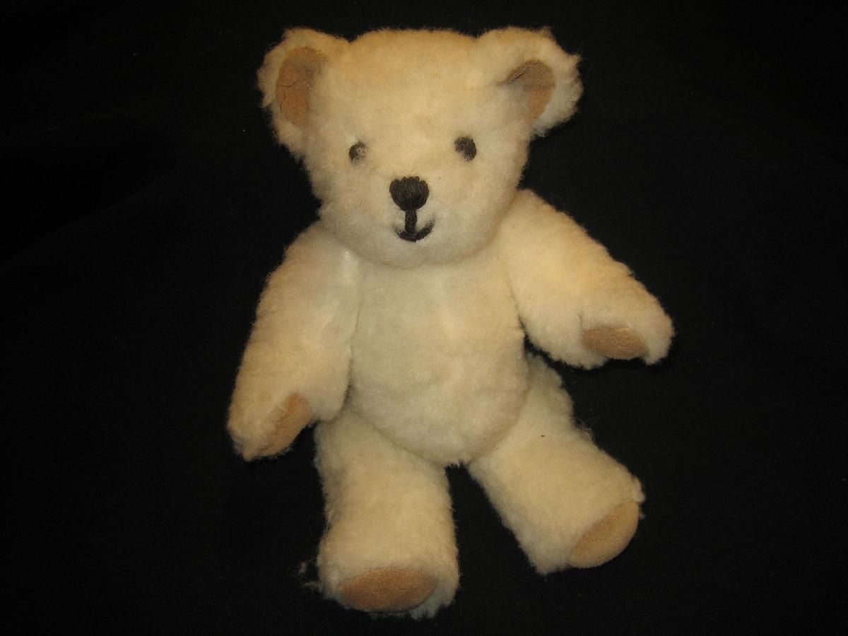 """Nallebjörn i vit ullteddy med fotdynor och öron av skinn och nos och ögon är broderade med svart ullgarn. Både armar och ben är ledade. En etikett är påsydd i nacken med texten """"SVENSK SLÖJD, Skaraborgs hemslöjd, SKÖVDE"""""""